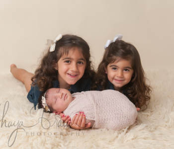 sisters and newborn baby