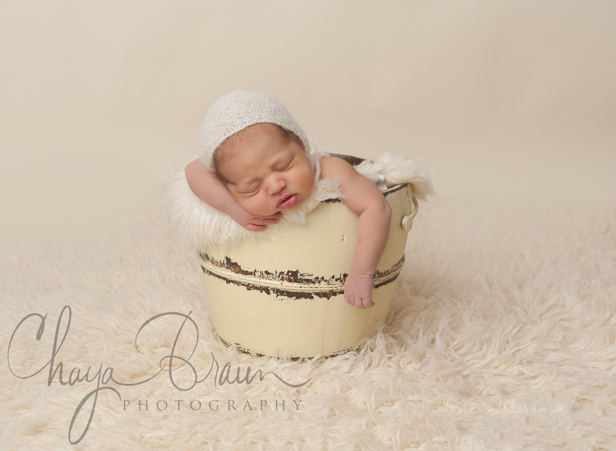 sleeping newborn baby in a bucket
