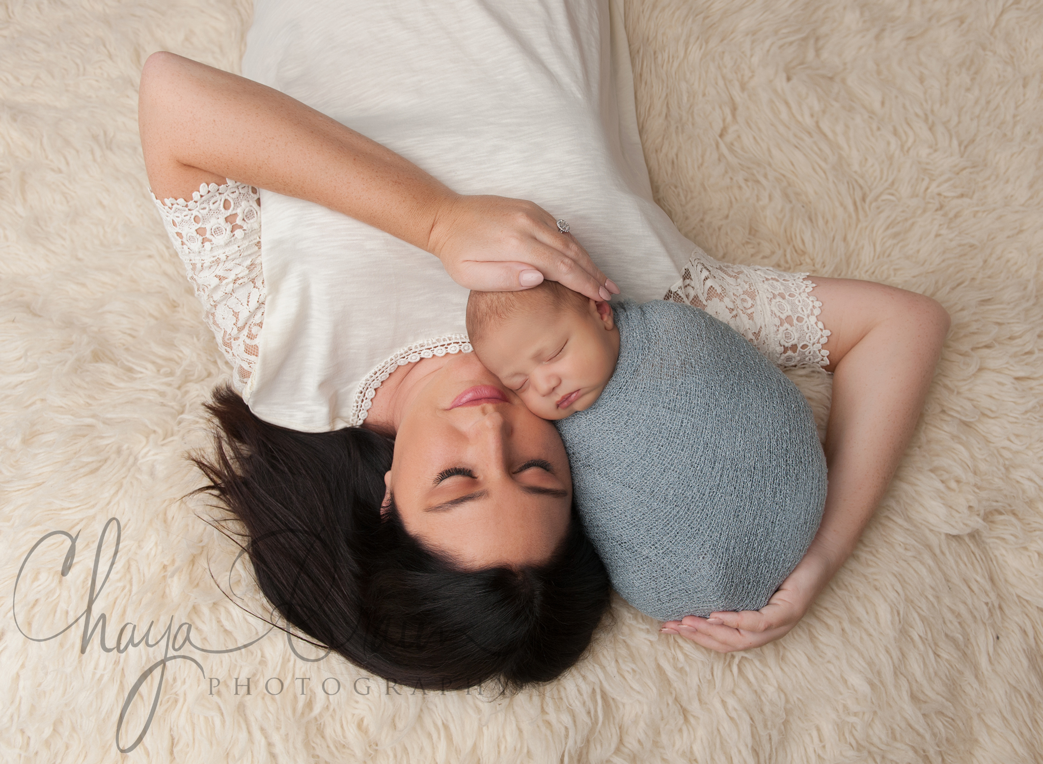 newborn baby and mom lying on rug
