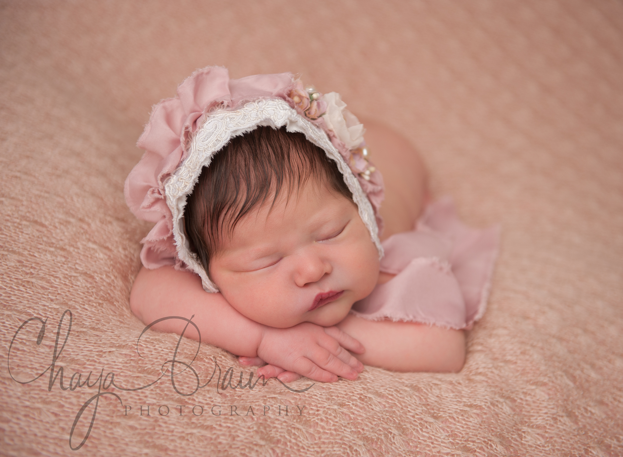 Sleeping newborn baby girl in pretty bonnet