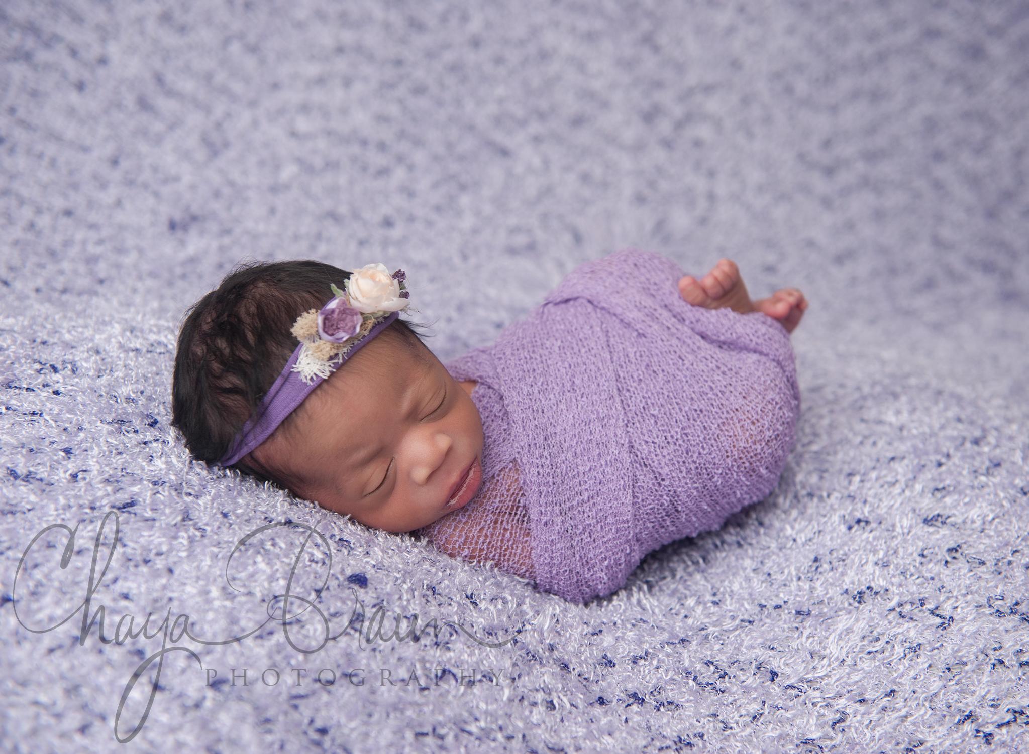 sleeping newborn girl in purple
