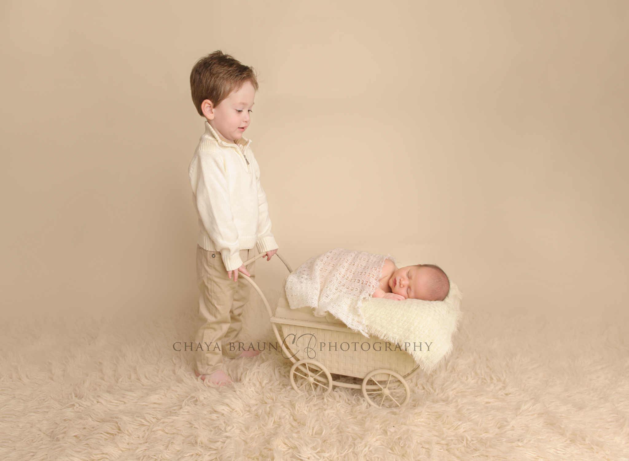 sibling pushing newborn in pram