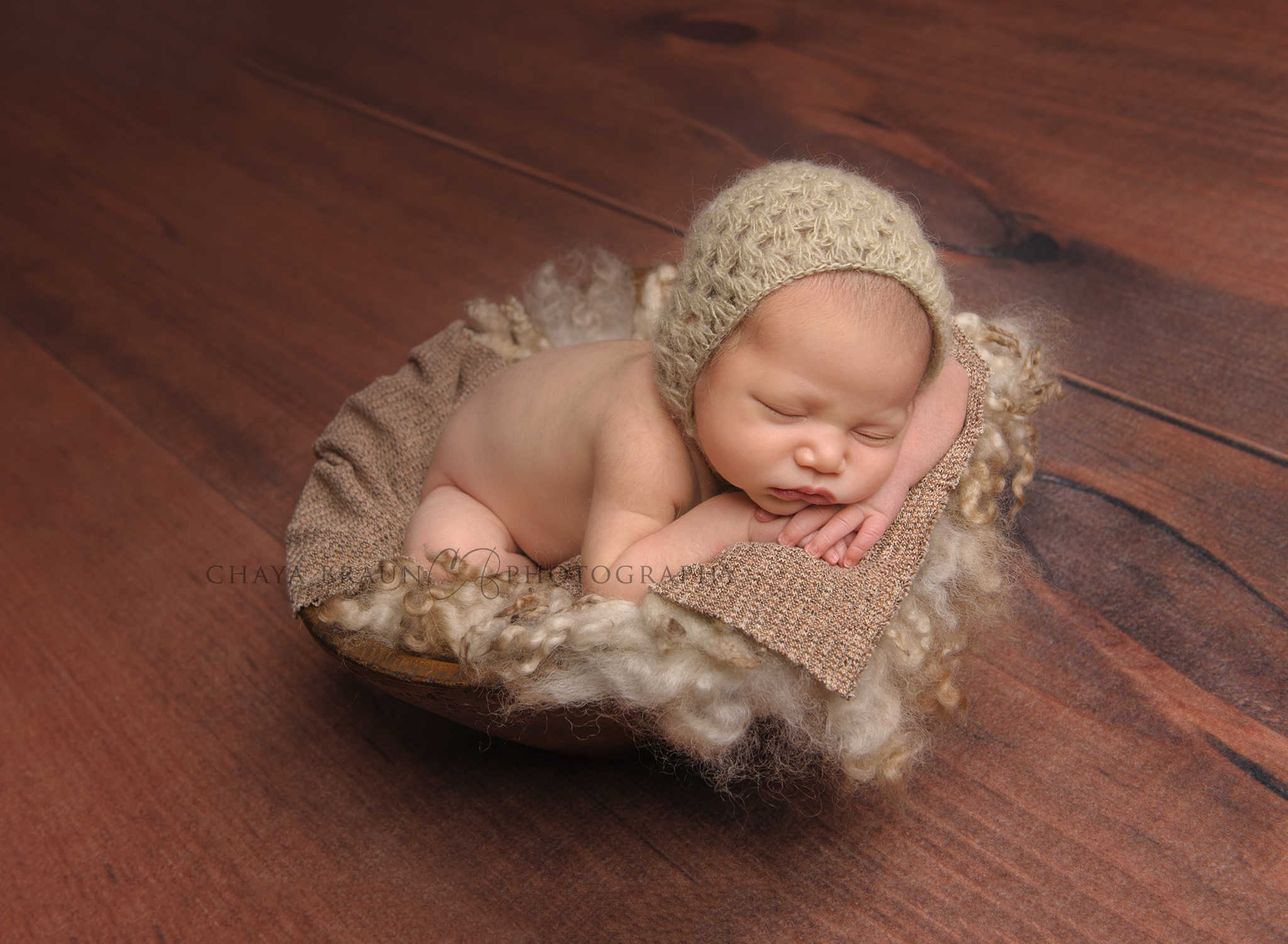 baby posed head on hands in basket