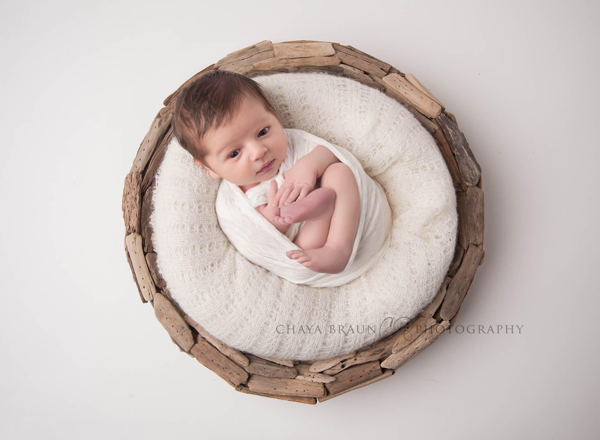 awake newborn baby in driftwood basket