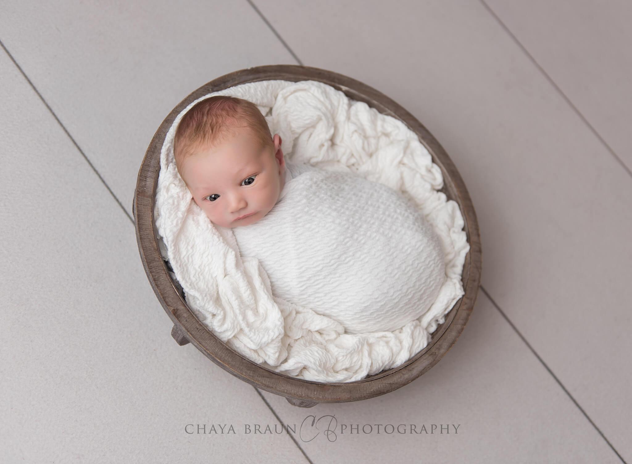 newborn baby in basket awake