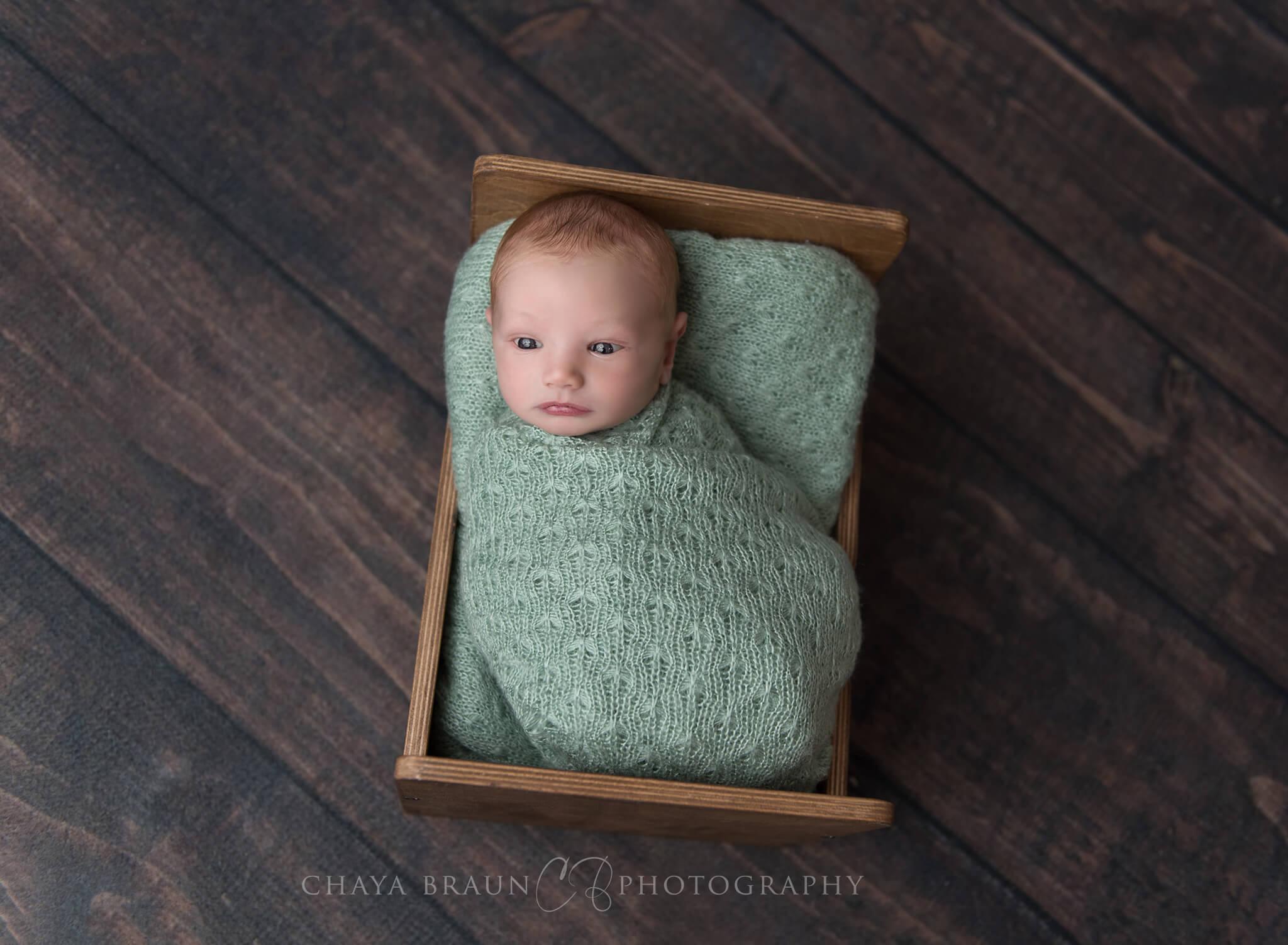 newborn baby in little crib